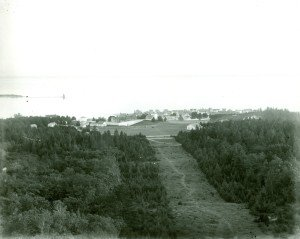 View of Fort Mackinac from Fort Holmes, ca. 1900. A portion of the grandstand is visible at the far left of the parade ground.  Sergeants' Quarters and the roof of Mon-commissioned Officers' Quarters are visible at the bottom right of the parade ground.