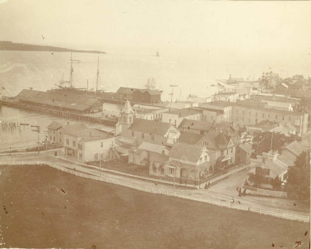The New Mackinac Hotel can be seen at the right center of this 1899 view. This provides a good view of back wing, kitchen wing, ice house, and a water tank at the very rear of the building.