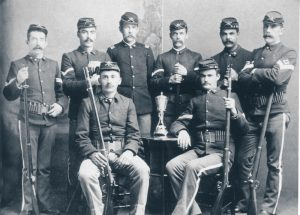 The Fort Mackinac rifle team in 1886, proudly displaying their trophy and their mustaches.