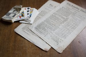 Under the Stamp Act of 1765, newspapers, playing cards, and other paper products were required to have an official stamp on them. Red tax stamps are visible on the bottom of these original newspapers on display at Michilimackinac.