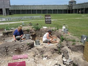 Janie is excavating 1781 demolition rubble and the mystery trench is behind John.