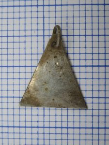 A small triangle of trade silver, discovered Wednesday afternoon, July 12. It appears to have been part of an earring or pendant. Trade silver is an excellent marker for the British era of the fur trade. This came from the interior of the house.