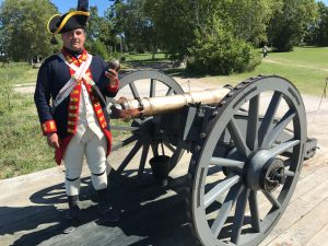 Light bronze 6-pound guns, mounted on highly mobile traveling carriages, made up the part of the early British defenses of Fort Mackinac. Here, a bombardier of the Royal Regiment of Artillery holds a 6-pound cannonball, which gives the weapon its name.