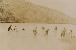 Soldiers of the 23rd Infantry using a net to catch fish in the Devil's River in Texas in 1898. Most of the men are wearing their blue shirts, but the second soldier from the left appears to be wearing his undershirt. The men wearing light-colored pants could just be wearing their drawers into the river, but they might also be the white trousers authorized for summer wear in 1888.